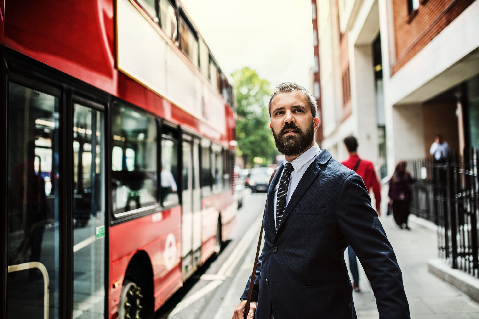Hipster businessman standing on the street, waiting for the bus in London.
